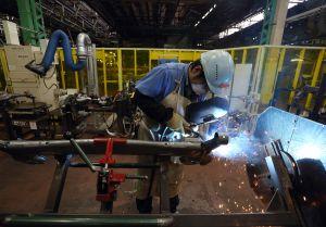 Toyota worker manually welding a part previously done by robots