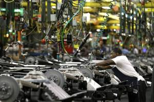 An auto worker assembles an SUV chassis at the Arlington, Texas, GM plant