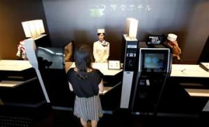 A receptionist robot, accompanied by two other robots, greets a hotel guest demonstrating how to check in the new hotel