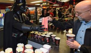 """A Darth Vader serves popcorn to fans on opening night of Walt Disney Pictures And Lucasfilm's """"Star Wars: The Force Awakens"""""""