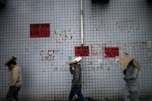 Workers walk past notices listing factory space for rent in Dongguan, a once thriving manufacturing hub.