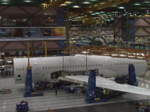 The wings are being installed onto the plane with heavy machinery