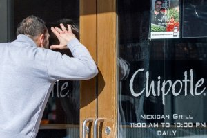 At lunchtime, people peered into a Chipotle in Washington, one of the stores that closed on Monday.