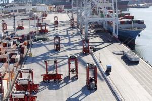 ". Cargo containers are carried around the Port of Los Angeles by automated machines guided by a magnetic grid embedded in the pavement. Autonomous ""straddle carriers,"" as they are known, pick up containers that have just come off the ship, and transport them to stacks to be organized. Automated machines pick up and carry cargo containers to stacks at the Port of Los Angeles, guided by a magnetic grid embedded in the pavement. A back-end technology system runs this robotic crane that sets containers in place in long stacks and retrieves them when truckers arrive to pick up the cargo. Cameras on the stacking crane assist workers in the port terminal office, guiding each container the last few feet to rest on a truck bed. Inside the port terminal office, a worker gently sets containers on truck beds using a joystick and live images of the machinery. On average, he loads more than one truck a minute in this way. Once they are off the ship, cargo containers at the TraPac terminal in Los Angeles are transported entirely by robots until they are set on trucks and carried off the terminal. Automated machines carry cargo containers around the TraPac marine terminal. Robotic cranes set containers in long stacks and retrieve them to load onto trucks. Cargo containers are carried around the TraPac marine terminal at the Port of Los Angeles by automated machines guided by a magnetic grid embedded in the pavement. PreviousNext 2 of 9 fullscreen Robotic cranes set containers in long stacks and retrieve them to load onto trucks. PATRICK T. FALLON FOR THE WALL STREET JOURNAL Autonomous ""straddle carriers,"" as they are known, pick up containers that have just come off the ship, and transport them to stacks to be organized"