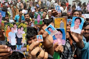 Relatives hold photos of workers missing in the Rana Plaza collapse