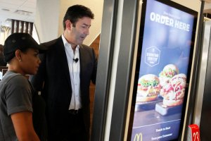 Steve Easterbrook, McDonald's chief executive, demonstrating how ordering is done at a self-service kiosk in NY