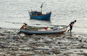 Indian fishermen pushed their boat through plastic waste last month in Mumbai.