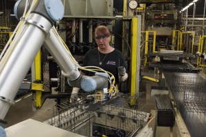Collaborative robots work on parts as employees assemble dishwater racks along an assembly line at a Whirlpool Corp. factory in Findlay, Ohio